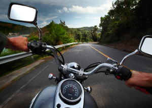 Rider driving motorcycle on a rural road in a mountains
